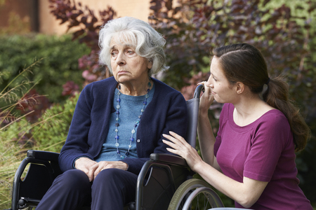 upset: Adult Daughter Comforting Senior Mother In Wheelchair Stock Photo