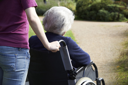 apoyo social: Hija Empujar senior madre en silla de ruedas