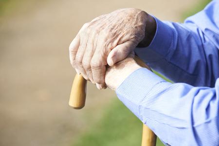 Close-up Van Senior Man's handen op wandelstok Stockfoto