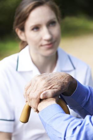carer: Senior Mans Hands Resting On Walking Stick With Care Worker In Background