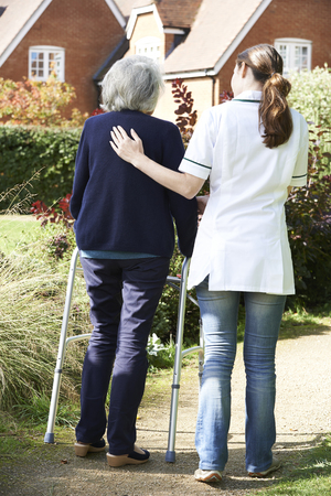 people from behind: Carer Helping Senior Woman To Walk In Garden Using Walking Frame