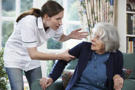 Cuidado Trabajador maltratar a la mujer mayor en el país Foto de archivo