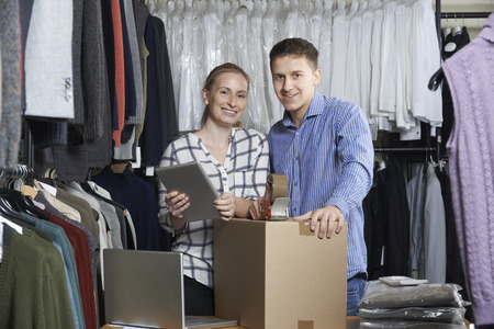 retail store: Couple Running On Line Clothing Store Packing Goods For Dispatch