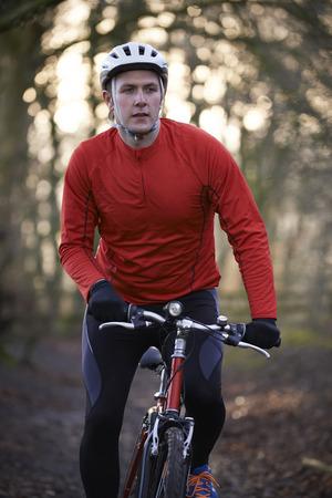 winter escape: Man Riding Mountain Bike Through Woodlands