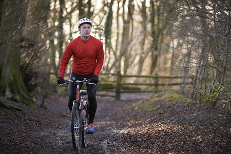the riding: Man Riding Mountain Bike Through Woodlands