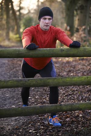 fitness men: Hombre que estira en la carrera a trav�s de arbolado del invierno