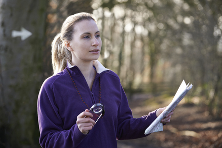 orienteering: Woman Orienteering In Woodlands With Map And Compass Stock Photo