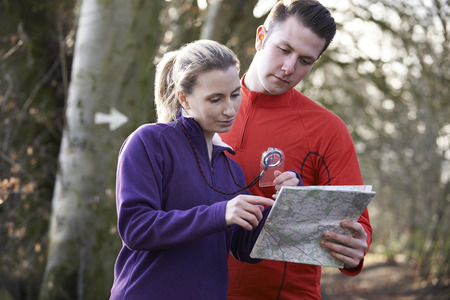 orienteering: Couple Orienteering In Woodlands With Map And Compass Stock Photo