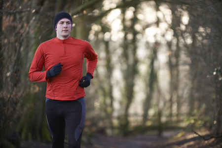 winter escape: Man On Winter Run Through Woodland Stock Photo