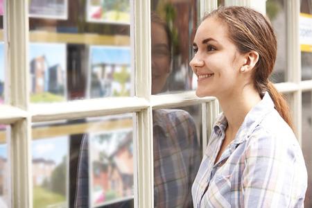 windows: Mujer sonriente joven que mira en la ventana de Agentes de Bienes Raíces