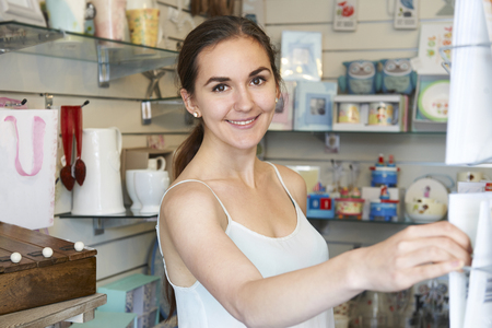Young Woman In Gift Shop Choosing Greetings Card photo
