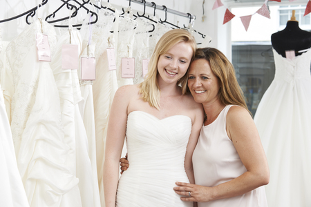 bride dress: Mother Helping Daughter To Choose Dress In Bridal Store Stock Photo