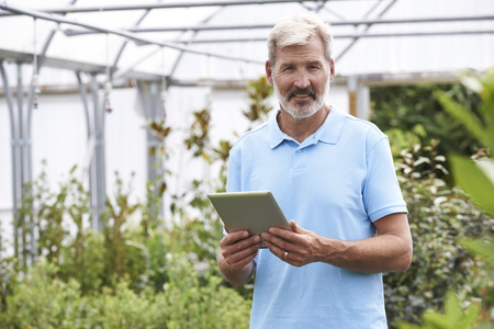 sales assistant: Portrait Of Sales Assistant In Garden Center With Digital Tablet