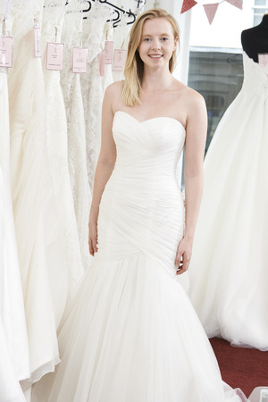 wedding dress: Bride Trying On Wedding Dress In Bridal Boutique Stock Photo