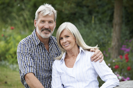 a couple: Portrait Of Mature Couple Relaxing In Garden Together
