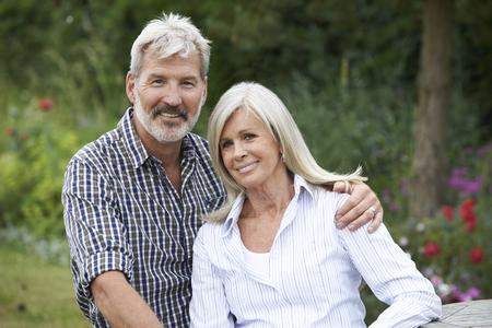 exteriores: Retrato de pareja madura que se relaja en jardín junto