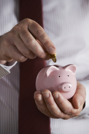 unrecognisable people: Businessman Putting Coin Into Piggy Bank
