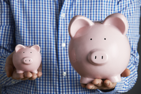 fourties: Man Holding Large And Small Piggy Bank