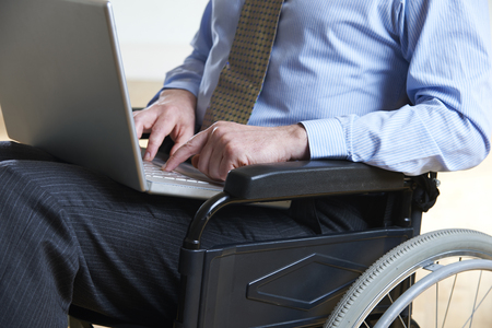 discapacidad: Hombre de negocios lisiado en sill�n de ruedas usando la computadora port�til Foto de archivo