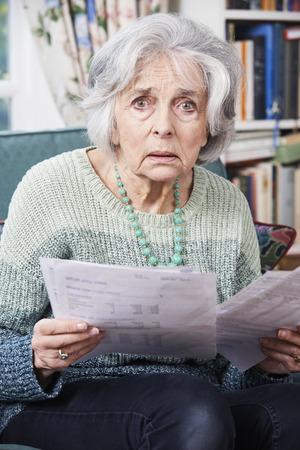 bills: Senior Woman Going Through Bills And Looking Worried Stock Photo