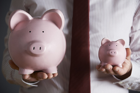 man holding money: Businessman Holding Large And Small Piggy Bank Stock Photo
