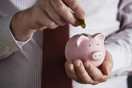 coin bank: Businessman Putting Coin Into Piggy Bank
