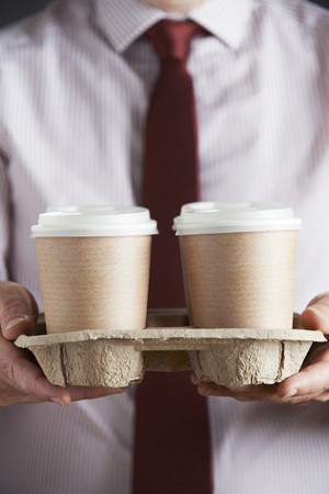 food and beverage: Businessman Holding Tray Of Takeaway Coffee