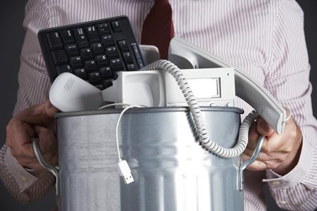 ferraille: Homme d'affaires Garbage Can Tenir Avec Obsolète Équipement de bureau Banque d'images