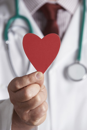 holding close: Close Up Of Doctor Holding Cardboard Heart