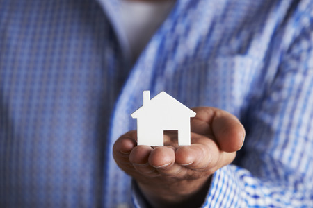unrecognisable people: Man Holding Model House In Palm Of Hand Stock Photo