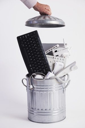 filling equipment: Businessman Filling Garbage Can With Obsolete Office Equipment Stock Photo