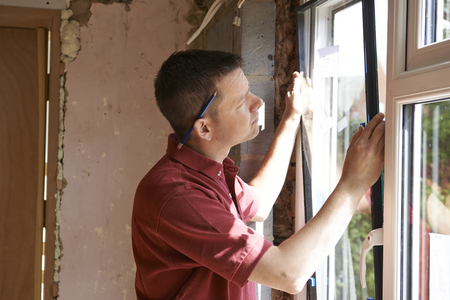 fitting: Construction Worker Installing New Windows In House Stock Photo