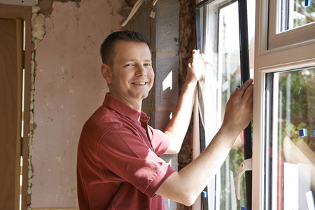 building contractor: Construction Worker Installing New Windows In House Stock Photo