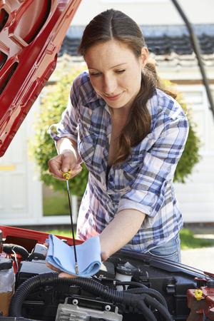 ディップスティックのフードの下で車のエンジン オイルのレベルをチェックする女性 写真素材