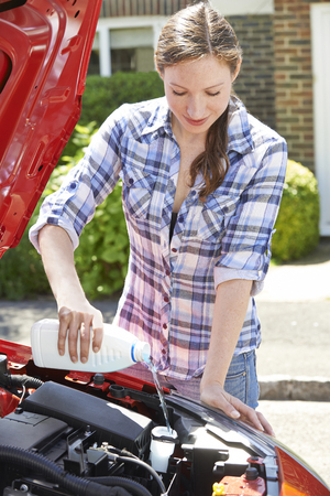 fluid: Woman Topping Up Windshield Washer Fluid In Car Stock Photo
