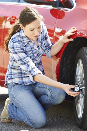 flat tyre: Woman Checking Car TyrePressure Using Gauge