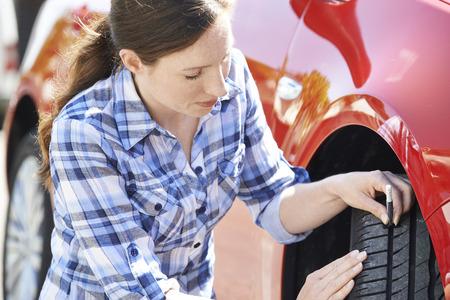 rodamiento: Mujer que controla la banda de rodadura de los neumáticos en el coche con manómetro