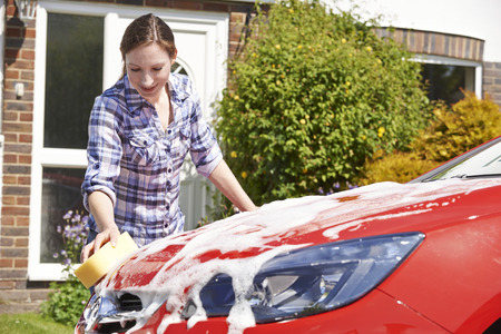 Woman Washing Car Outside House