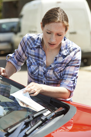 windscreen wiper: Frustrated Female Motorist Looking At Parking Ticket Stock Photo