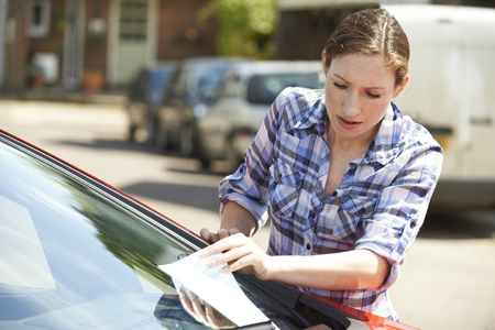 traffic ticket: Frustrated Female Motorist Looking At Parking Ticket Stock Photo