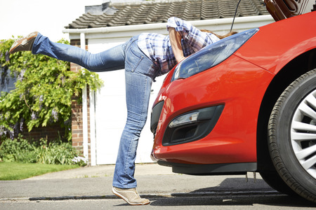 engine bonnet: Woman Looking At Car Engine With Head Disappearing Under Hood