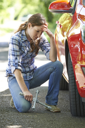 flat tire: Frustrated Female Driver With Tyre Iron Tring To Change Wheel