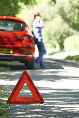emergency call: Female Driver Broken Down On Country Road With Warning Sign In Foreground