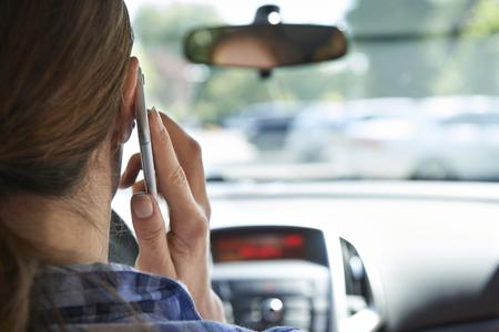 manejando: Mujer en el coche que habla en el teléfono móvil durante la conducción
