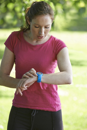 checking time: Female Runner In Park Checking Time Using Stopwatch