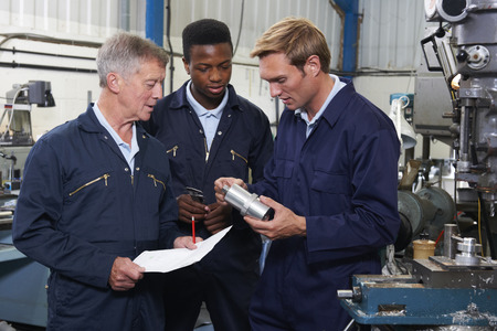 work man: Team Of Engineers Having Discussion In Factory Stock Photo