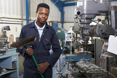 african american boy: Apprentice In Engineering Factory Sweeping Floor