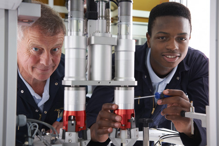 teenage guy: Engineer And Apprentice Working On Machine In Factory