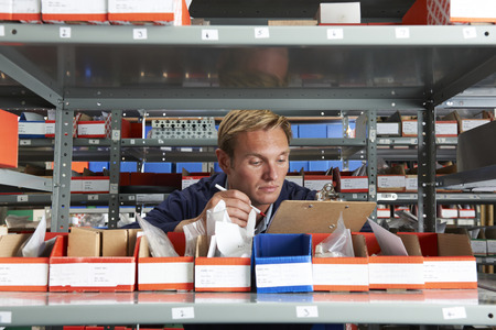 inventory: Factory Worker In Store Room Checking Stock Stock Photo