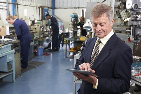 Inhaber der Maschinenfabrik mit digitalen Tablet mit Mitarbeitern im Hintergrund